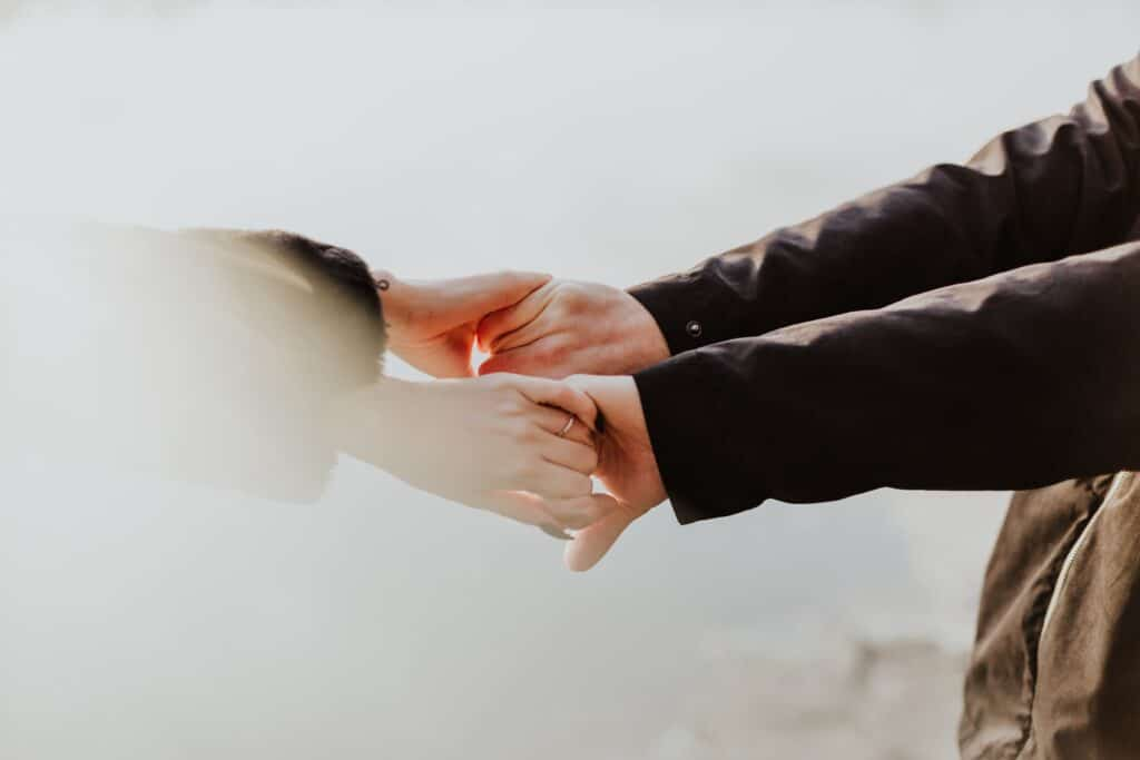 an image of two people holding hands after learning how to support someone in recovery
