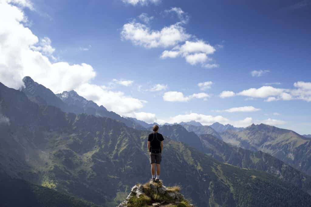 an image of a man on a mountain who learned how to overcome addiction