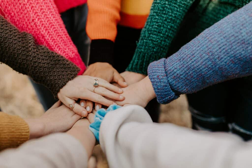 an image of people holding hands after learning how to help a drug addict